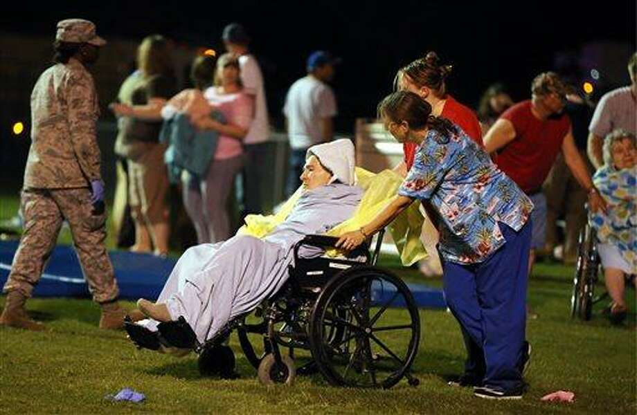 Emergency workers assist an elderly person at a staging area at a local school stadium Wednesday, April 17, 2013, in West, Texas. An explosion Wednesday night at a fertilizer plant near Waco sent flames shooting high into the night sky, leaving the factory a smoldering ruin, causing major damage at nearby buildings and injuring numerous people. (AP Photo/Waco Tribune Herald, Rod Aydelotte) Photo: AP / Waco Tribune Herald