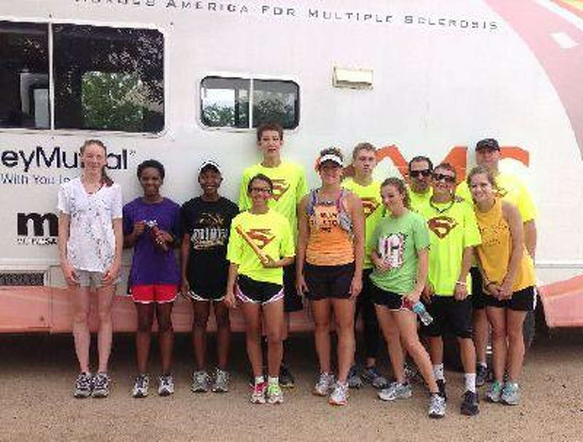 Wisconsin resident Amy VanDyke, center, is shown with Brush High School cross country runners and their coach, Jeff Marcus, back row second from right. The high school-ers escorted VanDyke into Brush on her leg of the MS Run the U.S. fundraising relay for research into curing multiple sclerosis. (Photo courtesy Jeff Marcus)