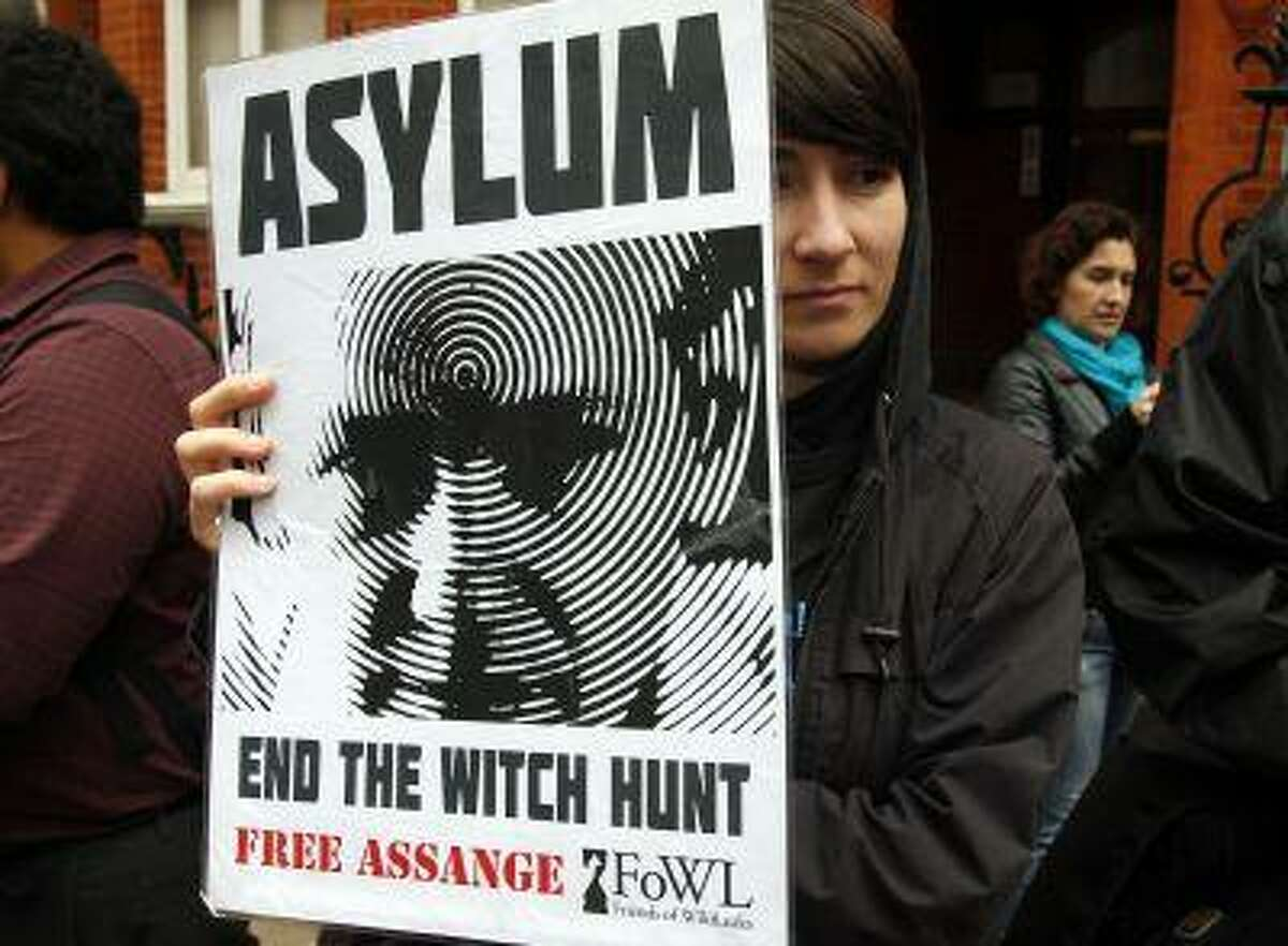 A supporter of WikiLeaks founder Julian Assange stands outside Ecuador's embassy, as she waits for Assange to appear on the the balcony, in central London June 16, 2013.
