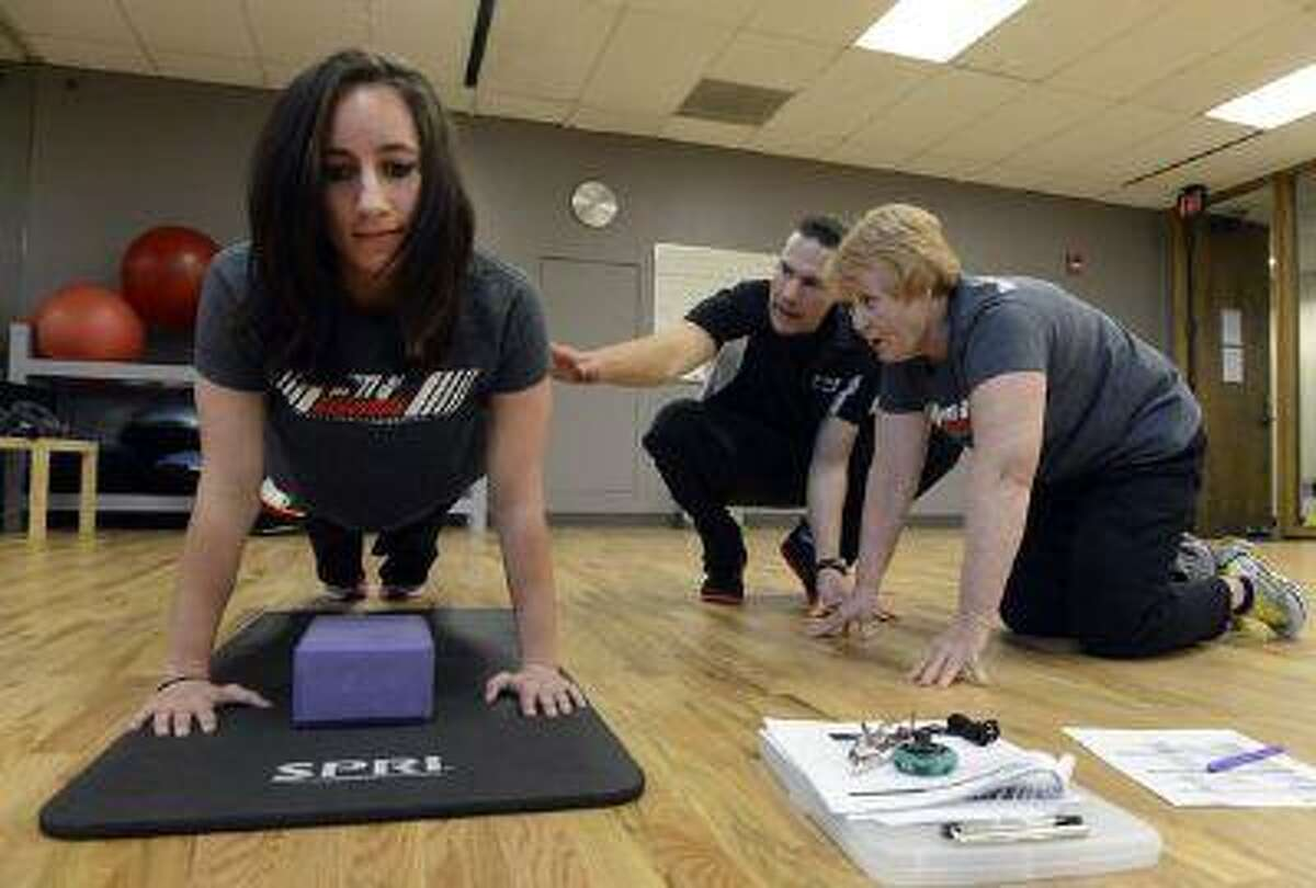 Deena Christy, 61, (right) of Letts, Iowa, works with National Personal Training Institute of Colorado instructor Shawn Agnew (center) on analyzing fellow student Ashli Bradley during a push-up test at the institute in Lakewood. Both Christy and Bradley are learning to become personal trainers.