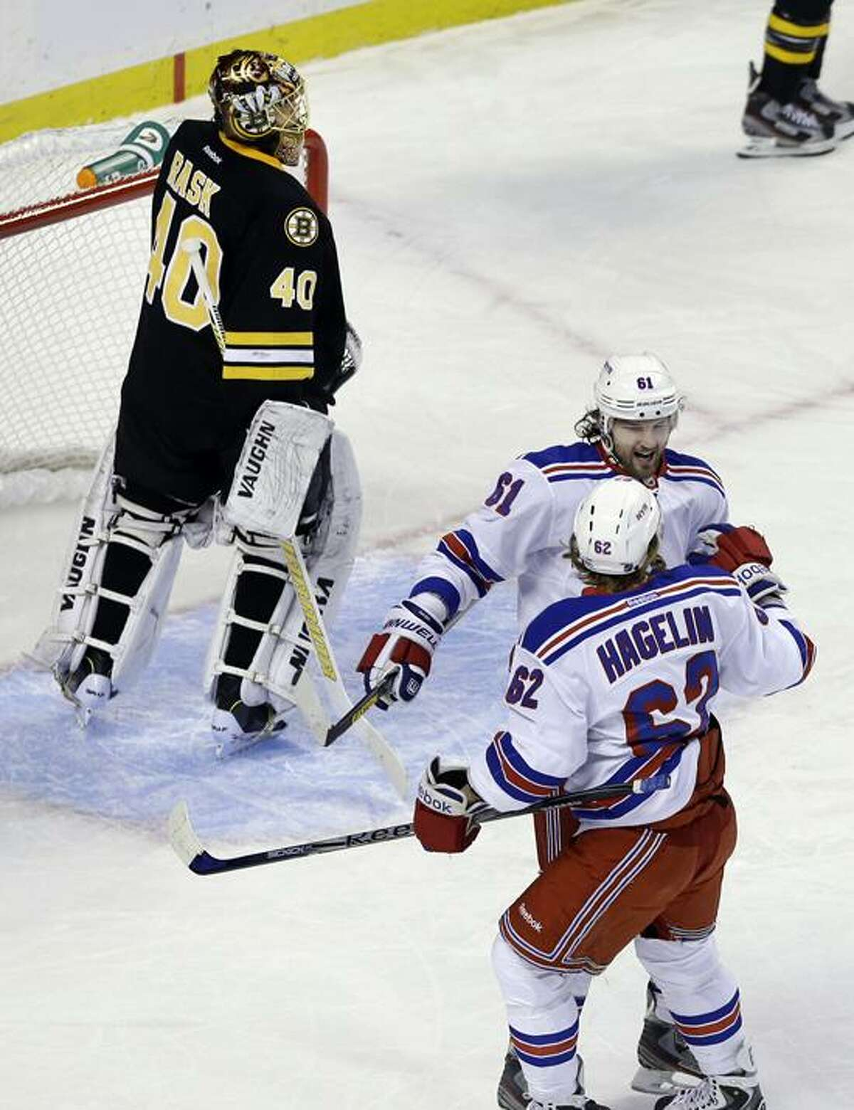 New York Rangers left wing Carl Hagelin (62) celebrates his goal with left wing Rick Nash (61) as Boston Bruins goalie Tuukka Rask (40) reacts during the first period of an NHL hockey game in Boston, Tuesday, Feb. 12, 2013. (AP Photo/Elise Amendola)