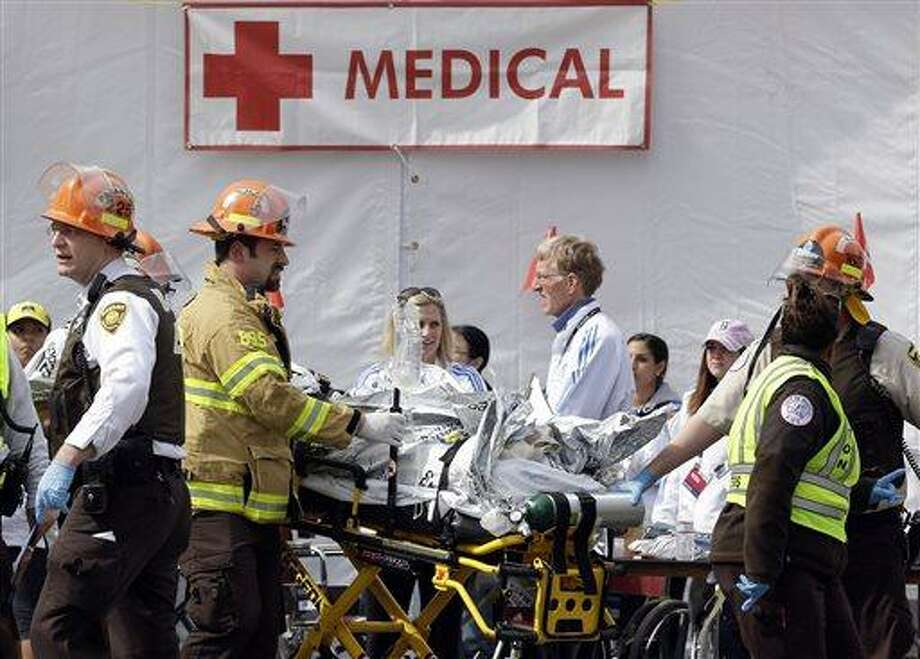 Medical personnel work outside the medical tent in the aftermath of two blasts which exploded near the finish line of the Boston Marathon in Boston, Monday, April 15, 2013. (AP Photo/Elise Amendola) Photo: AP / AP