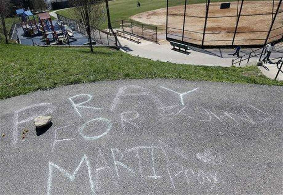 """""""Pray for Martin"""" is written in chalk at a park near the home of Martin Richard in the Dorchester neighborhood of Boston,Tuesday, April 16, 2013. 8-year old Martin was killed in the bombing at the finish line of the Boston Marathon on Monday. (AP Photo/Michael Dwyer) Photo: AP / AP"""