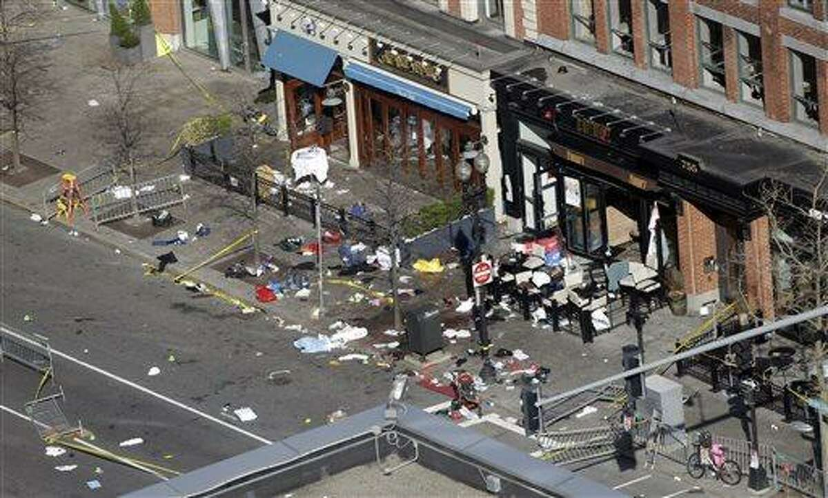 One of the blast sites on Boylston Street near the finish line of the 2013 Boston Marathon is seen in Boston, Tuesday, April 16, 2013, one day after bomb blasts killed three and injured over 140 people. FBI agents searched a suburban Boston apartment overnight and appealed to the public for amateur video and photos that might yield clues to who carried out the Boston Marathon bombing. (AP Photo/Elise Amendola)