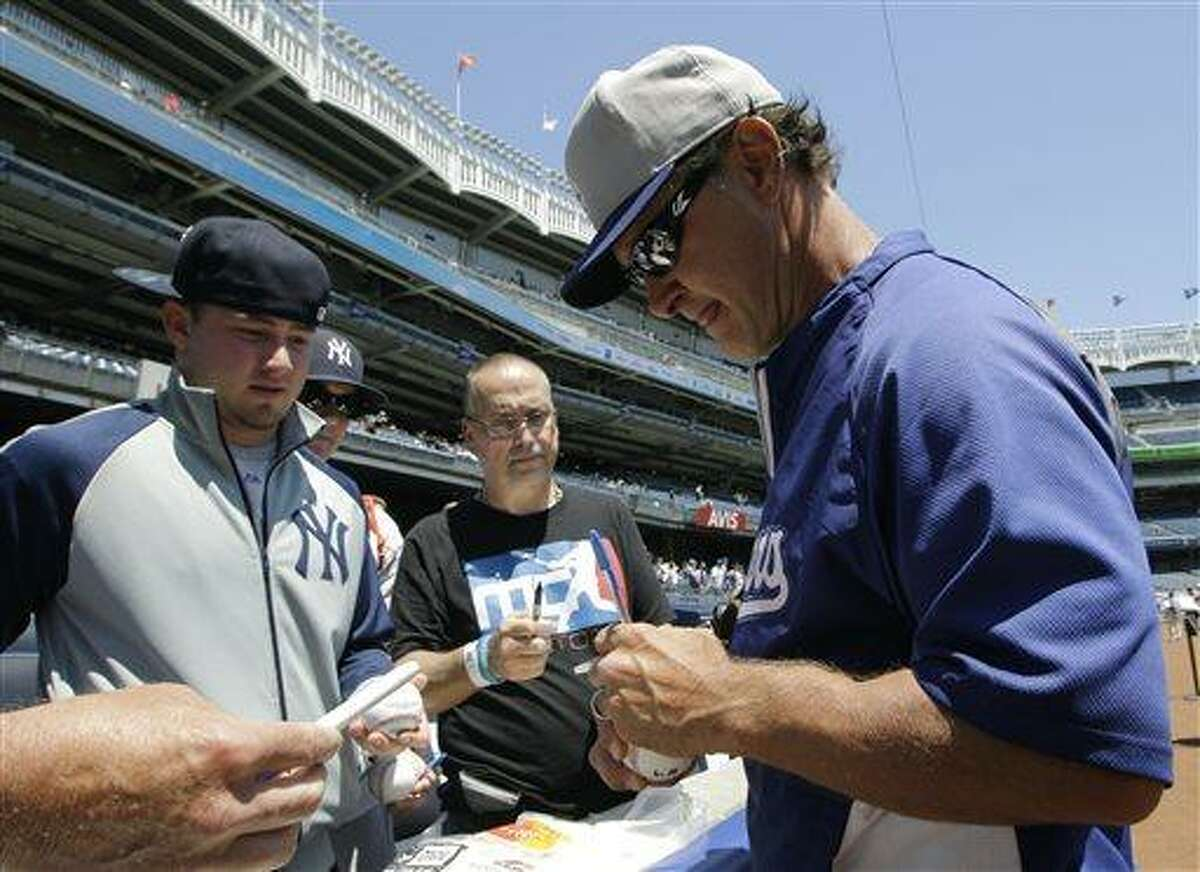 Los Angeles Dodgers manager Don Mattingly signs autographs for fans at Yankee Stadium before a baseball game against the New York Yankees Wednesday, June 19, 2013, in New York. (AP Photo/Kathy Willens)