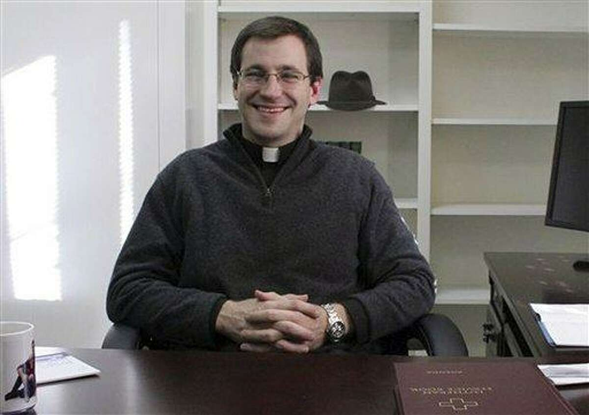 In this January 2012 photo provided by the Newtown Bee, the Rev. Rob Morris sits in his office at Christ the King Lutheran Church in Newtown, Conn. The Lutheran Church-Missouri Synod denomination is reprimanding Rev. Morris for participating in an interfaith vigil on Dec. 16, 2012, after the Sandy Hook massacre. The denomination bars joint worship because it doesn't want to appear to mix its beliefs with those of other faiths. AP Photo/Newtown Bee, Shannon Hicks