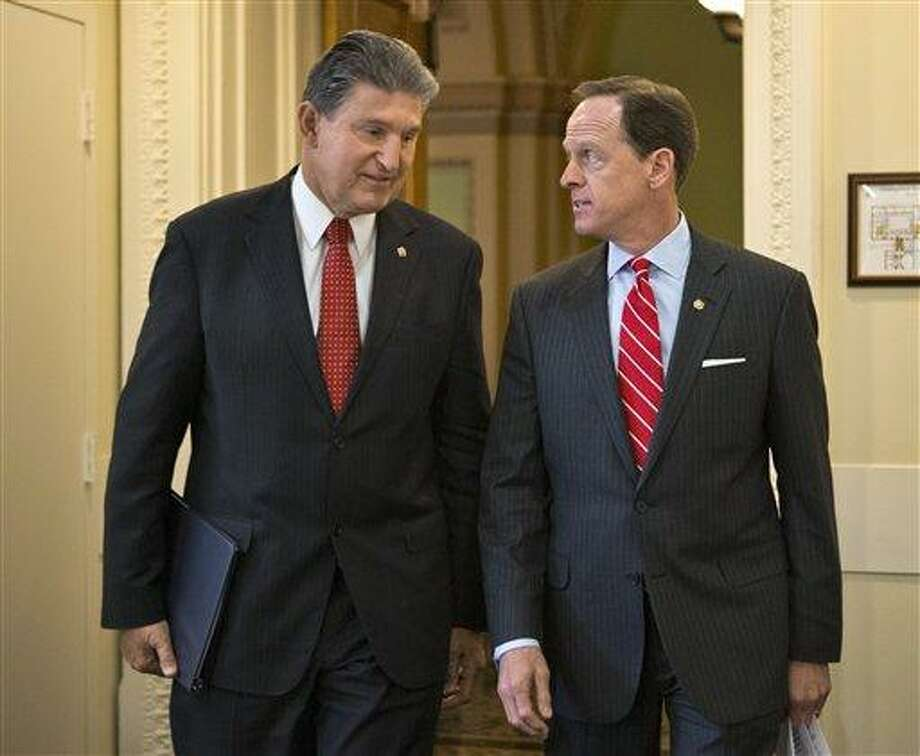 """Sen. Joe Manchin, <a href=""""http://D-W.Va"""">D-W.Va</a>., left, and Sen. Patrick Toomey, R-Pa. arrive April 10 for a news conference on Capitol Hill in Washington to announce that they have reached a bipartisan deal on expanding background checks to more gun buyers. Associated Press file photo Photo: AP / AP"""