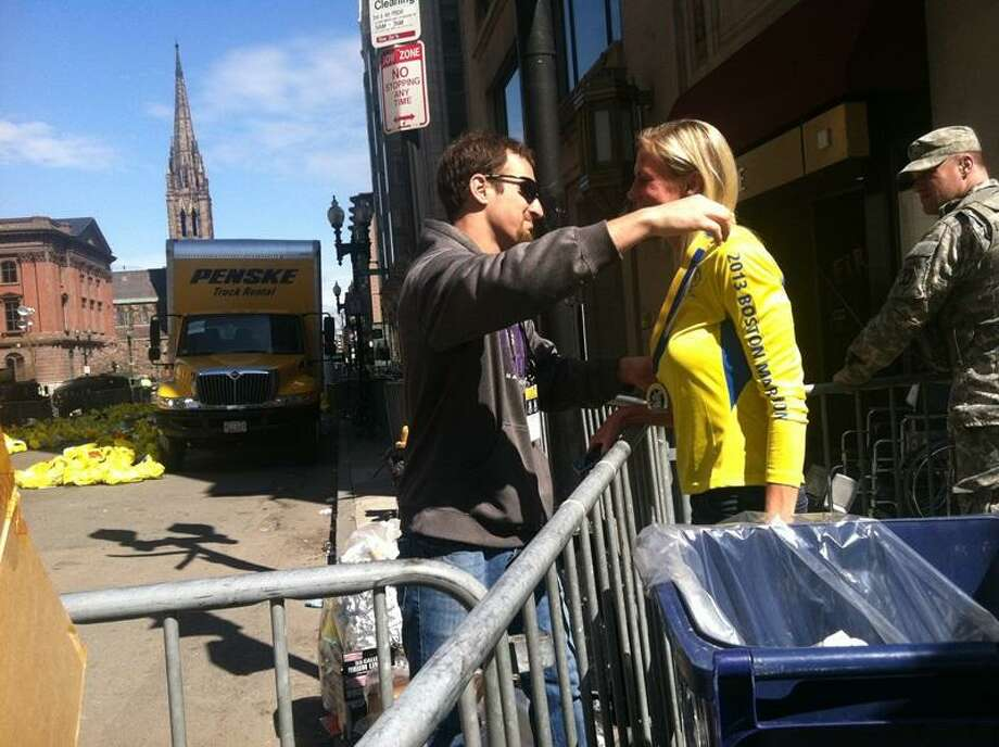A volunteer puts a medal around the neck of a Boston Marathon runner. Jennifer Swift/for the New Haven Register
