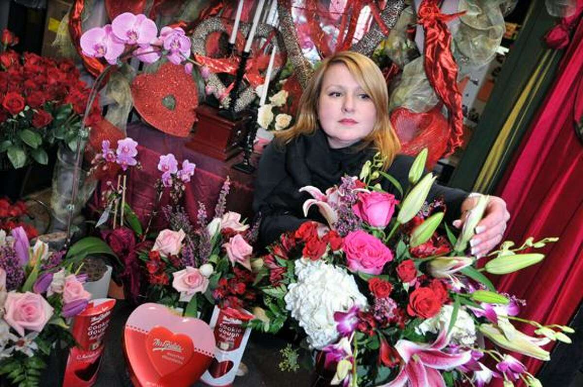 Catherine Avalone/The Middletown PressVirginia Wade-Fralick, co-owner and floral designer of Wild Orchid LLC at 413 Main Street in Middletown adds orchids and lilies to an arragement Tuesday afternoon. Wade-Fralick who owns the flower shop with her sister Cynthia Wade Wolfram said the shop usually creates a couple of hundred Valentine's Day arrangements for both pick-up and deliveries and will be making deliveries on Thursday despite the snow.
