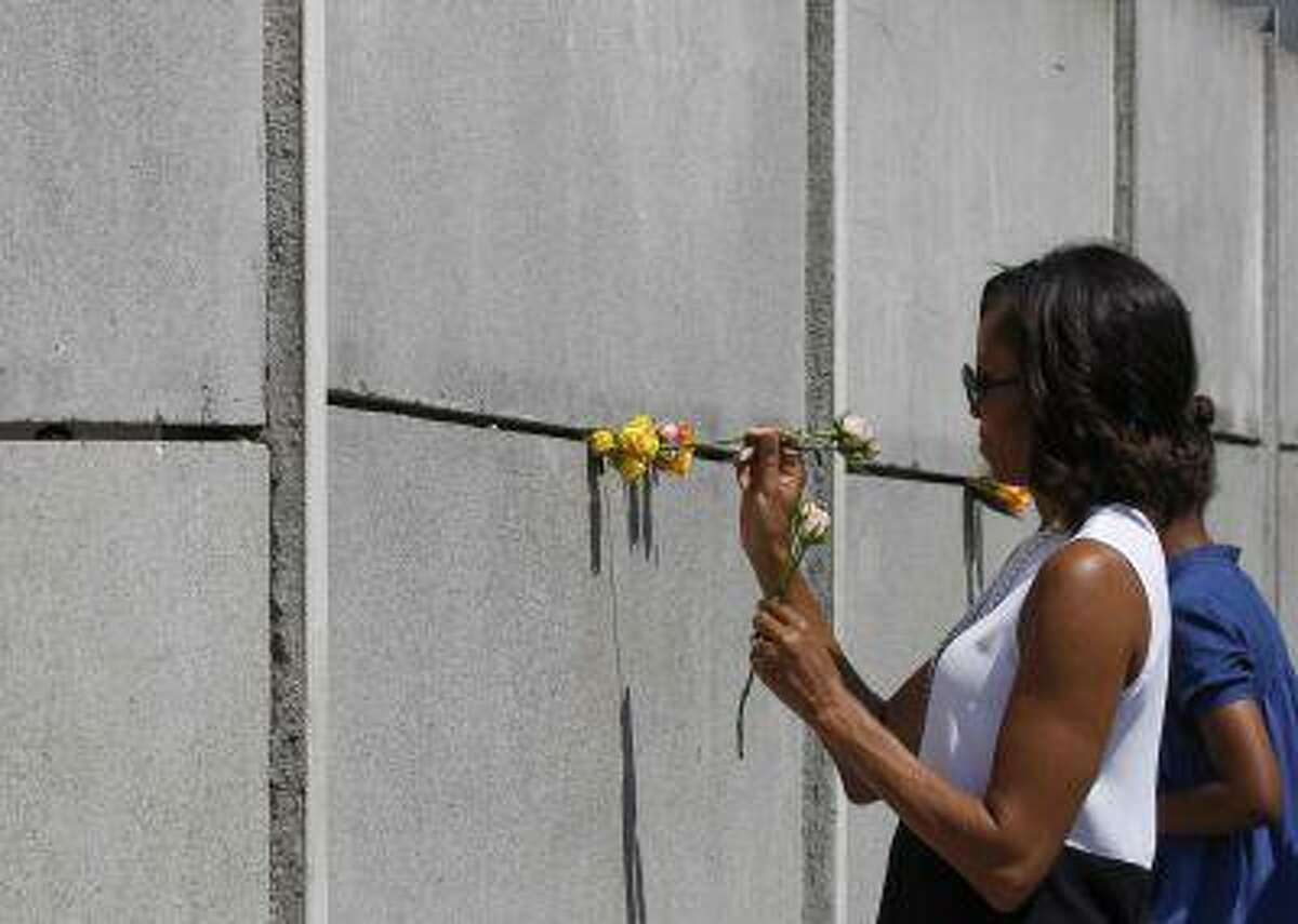 U.S. first lady Michelle Obama and her daughter Sasha place flowers as they visit the Berlin Wall memorial in Bernauer Strasse in Berlin June 19, 2013.