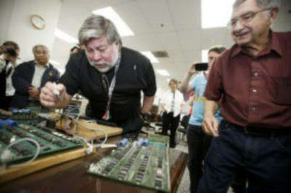 Steve Wozniak, center, co-founder of Apple, and Wendell Sander, right, one of Apple's early employees, signed their signature on some of remaining Apple 1 computers on June 18, 2013 at History San Jose. (Dai Sugano/Bay Area News Group)