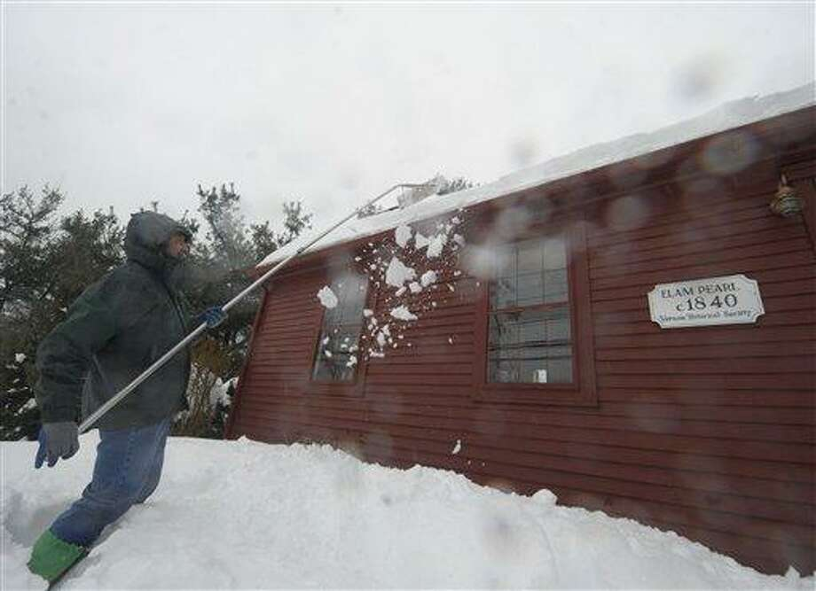 Al Brewer uses a snow rake to clear snow off the roof of his home that dates back to 1840,  as rain falls on Monday, Feb. 11, 2013,  in Vernon, Conn.  (AP Photo /Journal Inquirer, Jim Michaud) Photo: AP / Journal Inquirer