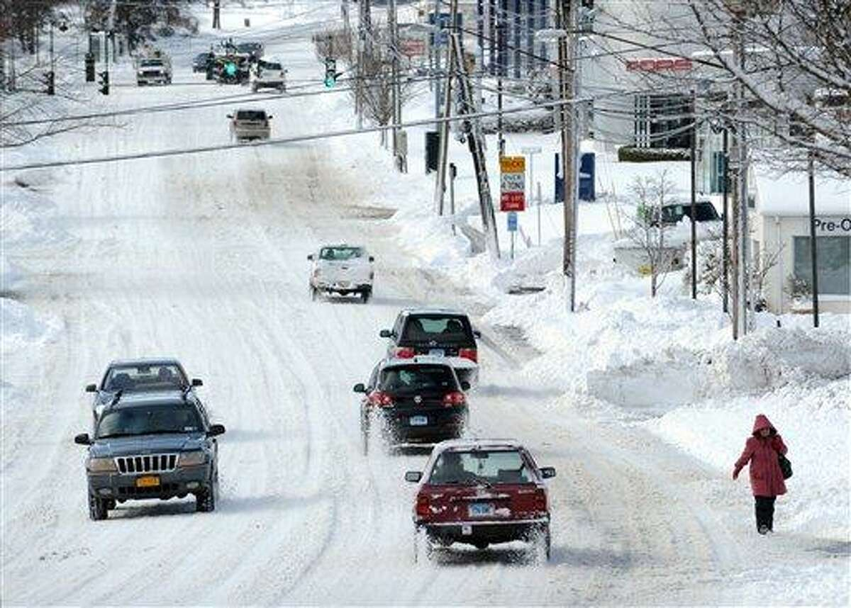 Cars drive along West Putnam Avenue during the aftermath of a blizzard in Greenwich, Conn., Saturday morning, Feb. 9, 2013. (AP Photo/Greenwich Time, Bob Luckey) MANDATORY CREDIT; MAGS OUT