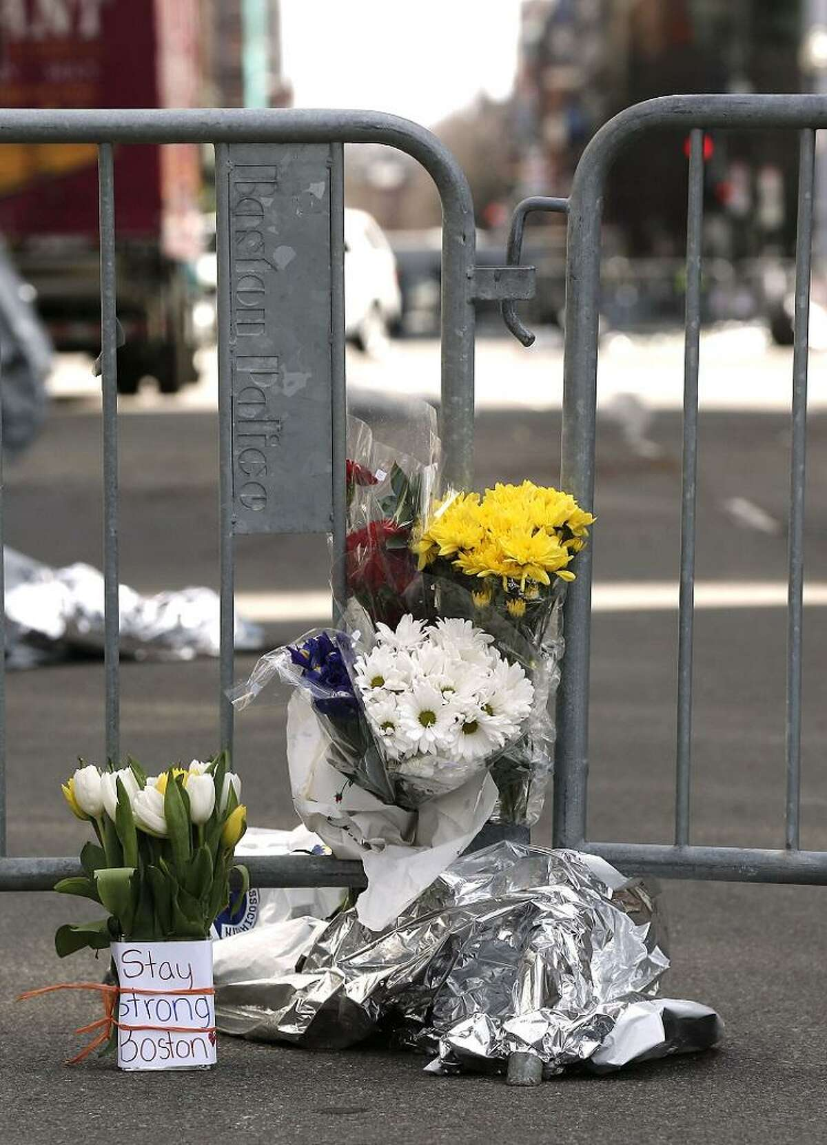 Flowers sit at a police barrier near the finish line of the Boston Marathon in Boston Tuesday, April 16, 2013. Explosions at the finish of the Marathon Monday Killed at least 3 people and injured over 170. (AP Photo/Winslow Townson)