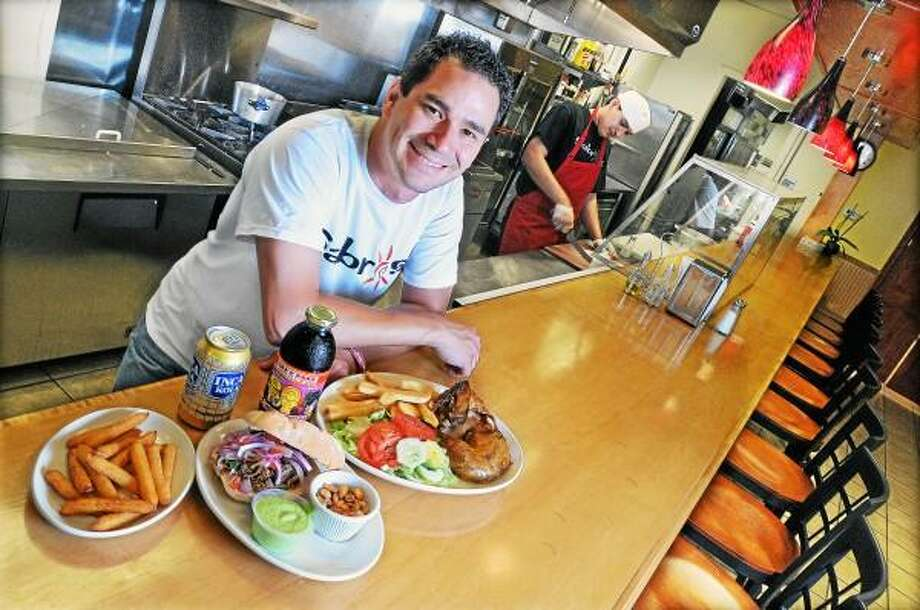 Catherine Avalone/The Middletown Press Duncan Olaechea, owner of Sabroso at 170 Main Street in Middletown serves yuca fries, roasted pork sandwich, rotisserie chicken, Peruvian green sauce, Inca Cola and Chicha Morada drinks at the Peruvian restaurant he owns with his mother, Maria Paquette. / TheMiddletownPress