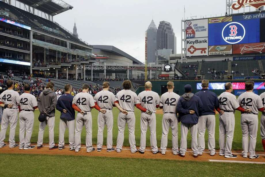 The Boston Red Sox players and coaches observe a moment of silence for the victims of the Boston bombings before a baseball game  against the Cleveland Indians Tuesday, April 16, 2013, in Cleveland. (AP Photo/Mark Duncan) Photo: AP / AP