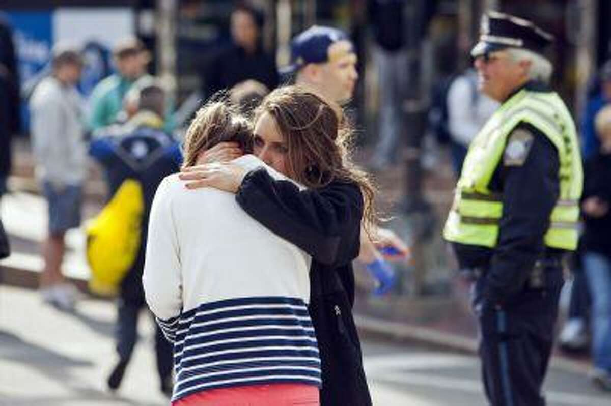 A woman comforts another, who appears to have suffered an injury to her hand, after explosions interrupted the 117th Boston Marathon in Boston, Massachusetts April 15, 2013. Two people were killed and 23 others injured after two explosions struck the Boston Marathon as runners crossed the finish line on Monday, Boston police said. REUTERS/Dominick Reuter (UNITED STATES - Tags: SPORT ATHLETICS DISASTER)