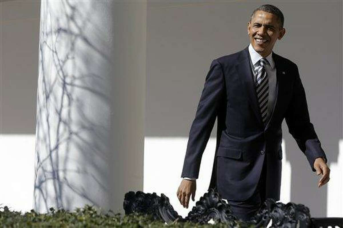 President Barack Obama looks towards reporters shouting questions as he walks down the West Wing Colonnade of the White House in Washington, Tuesday, Feb. 12, 2013, ahead of tonight's State of the Union speech on Capitol Hill. (AP Photo/Charles Dharapak)