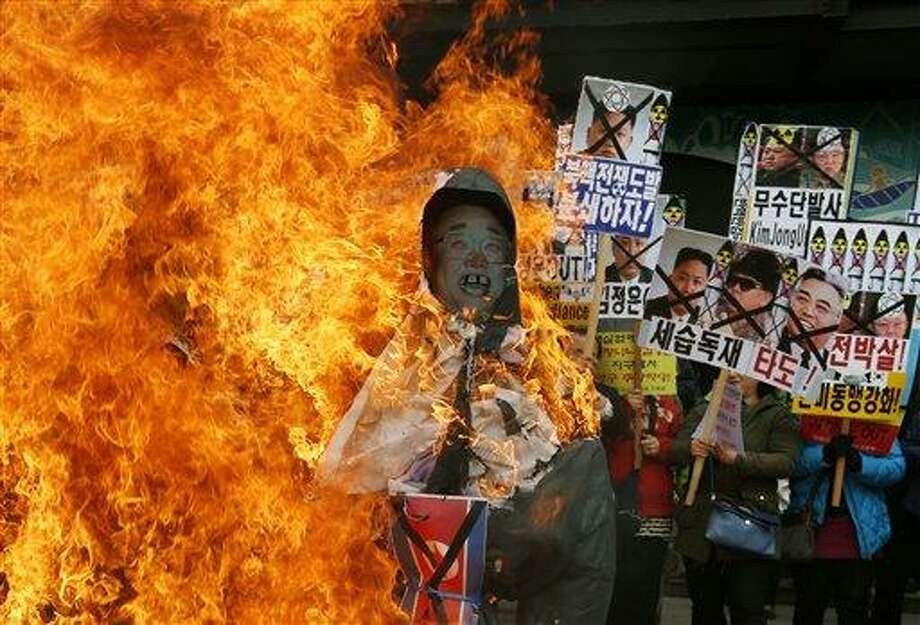 """FILE - In this April 15, 2013 file photo, South Korean protesters burn effigies of North Korean leader Kim Jong-Un, and late leaders Kim Jong Il and Kim Il Sung at an anti-North Korea protest on the birthday of Kim Il Sung in Seoul, South Korea. North Korea lashed out anew Tuesday, April 16, 2013 at South Korea over the small public protest, saying it would not hold talks with its southern neighbor unless it apologized for anti-North Korean actions """"big and small"""" and warning that it could take retaliatory measures at any time. The sign at center showing images of the Kim family reads """"Throw Them Out.""""  (AP Photo/Kin Cheung, File) Photo: AP / AP"""