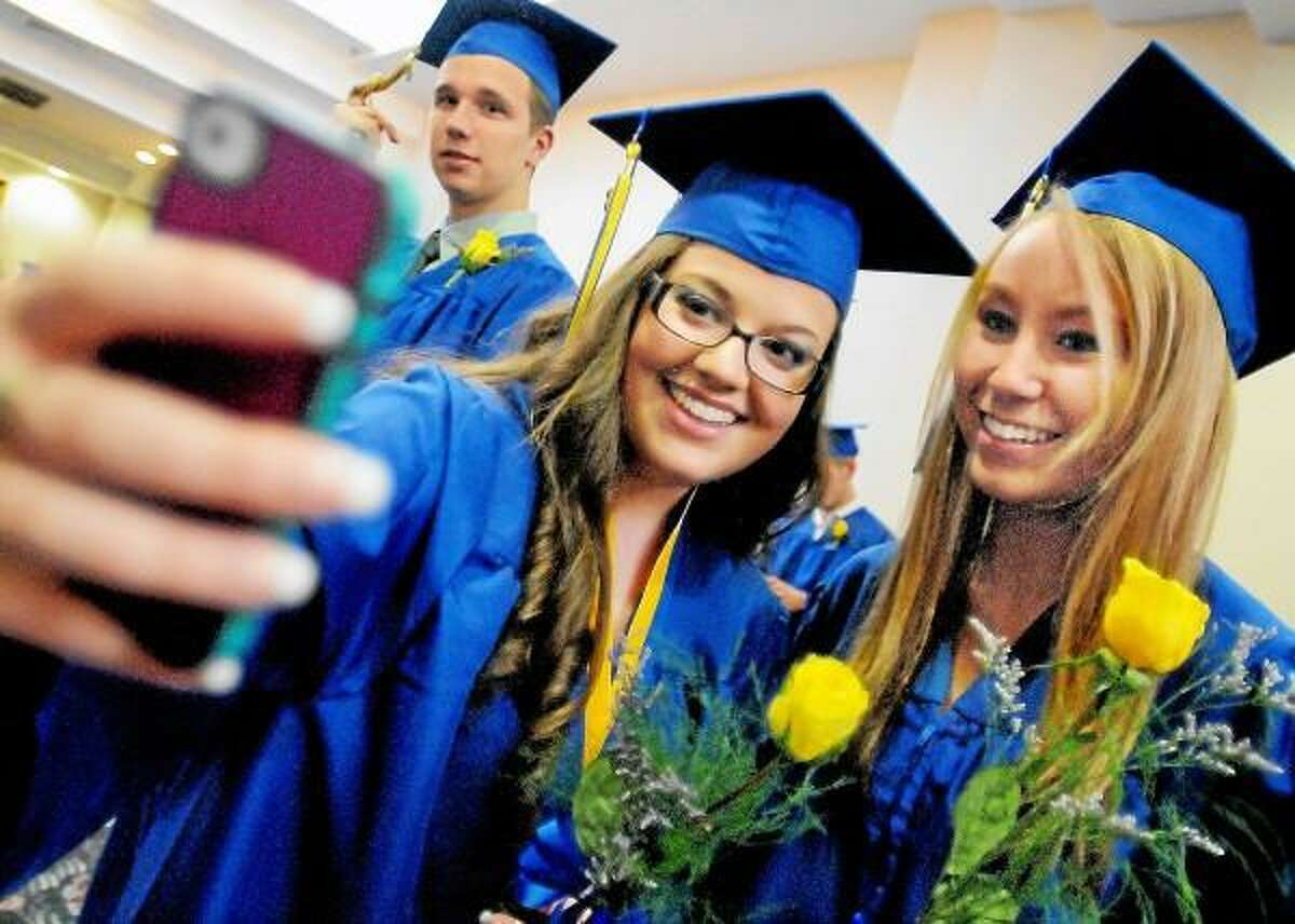 Catherine Avalone/The Middletown Press Samantha Misenti uses her phone to take a picture with her classmate Heather Zambrello, both members of Vinal Technical High School's class of 2013 shortly before the processional at commencement Wednesday evening in the Grand Ballroom at the Crowne Plaza Hotel and Convention Center in Cromwell. Misenti majored in Information Systems Technology and Zambrello in Hairdressing, Cosmetology & Barbering.