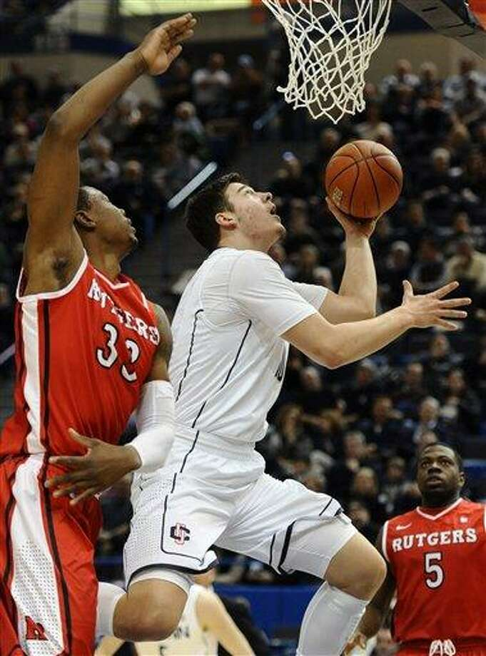 Connecticut's Tyler Olander, center, drives to the basket while guarded by Rutgers' Wally Judge, left, during the first half of an NCAA college basketball game in Hartford, Conn., Sunday, Jan. 27, 2013. (AP Photo/Jessica Hill) Photo: ASSOCIATED PRESS / A2013