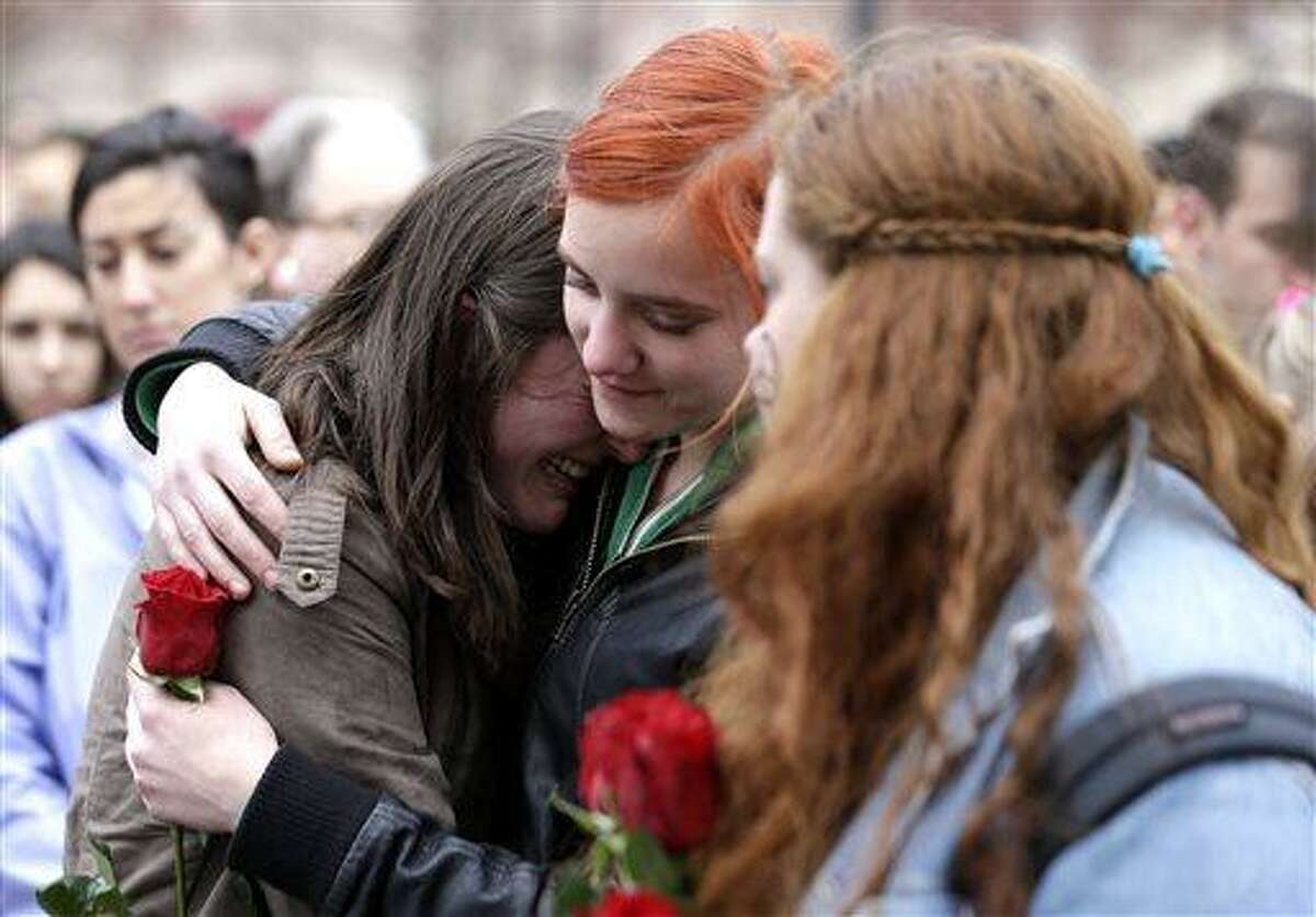 Emma MacDonald, 21, left, is comforted by Rachael Semplice, 22, center, as Juliana Hudson, 23, looks during a vigil for the victims of the Boston Marathon explosions at Boston Common, Tuesday, April 16, 2013. Twin explosions near the marathon's finish line Monday killed three people, wounded more than 170 and reawakened fears of terrorism. (AP Photo/Julio Cortez)