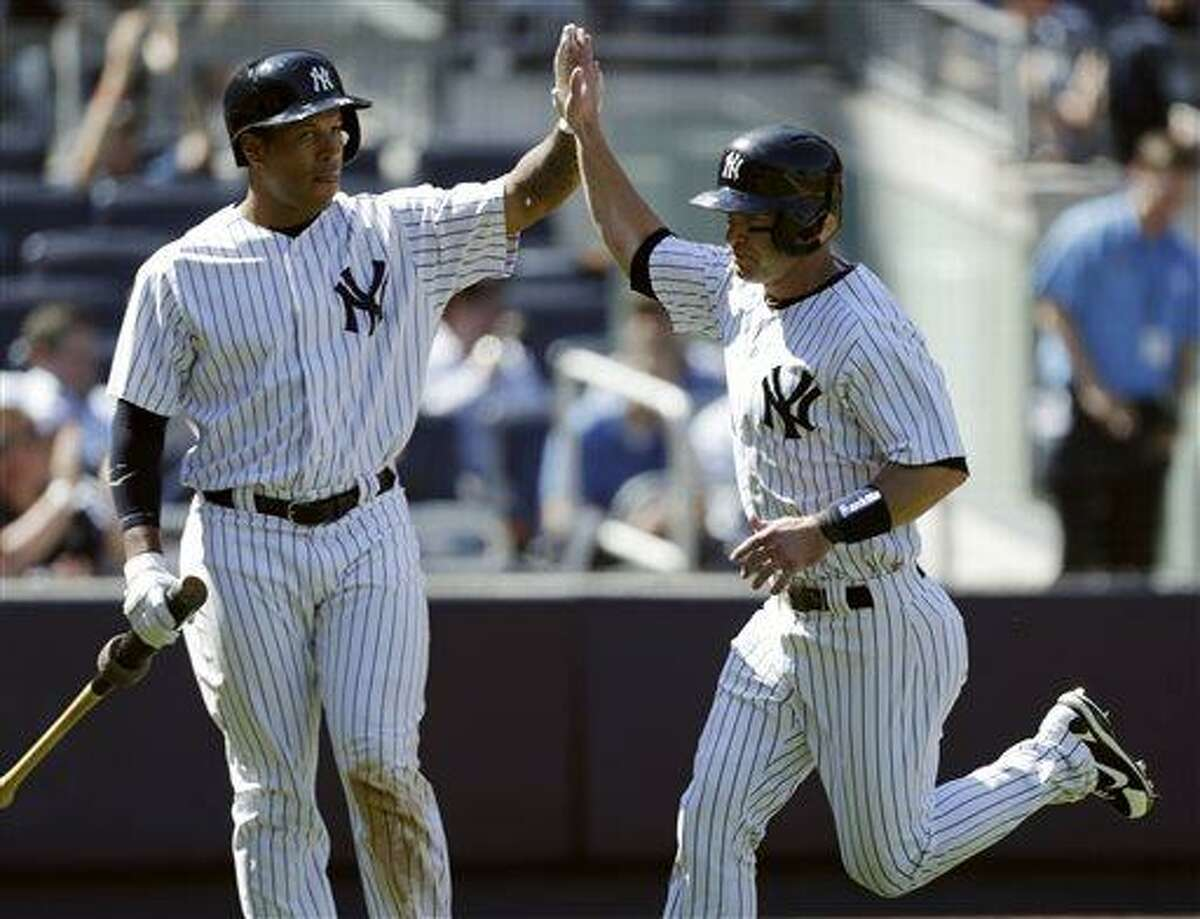 New York Yankees' Thomas Neal, left, greets Jayson Nix after Nix scored due to Los Angeles Dodgers relief pitcher Ronald Belisario's seventh-inning fielding error in the first game of a baseball doubleheader on Wednesday, June 19, 2013, in New York. (AP Photo/Kathy Willens)