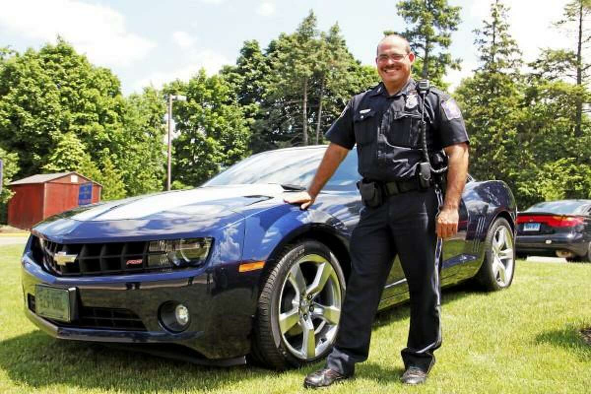 Officer Steven Cloutier stands next to his 2011 Chevy Camaro outside the Torrington Police Department on Wednesday, June 19, 2013. Cloutier is helping organize the Torrington Police Department Auto Show, which will take place on Friday starting at 5:30 p.m. on Main Street in Downtown. His car will be in the show, and more than 300 cars are expected. Esteban L. Hernandez Register Citizen