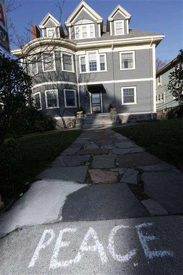Peace is written on the sidewalk in front of the Richard house in the Dorchester neighborhood of Boston, Tuesday, April 16, 2013.  Martin Richard, 8,  was killed in Monday's bombing at the finish line of the Boston Marathon. (AP Photo/Michael Dwyer) Photo: AP / AP