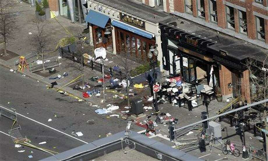 One of the blast sites on Boylston Street near the finish line of the 2013 Boston Marathon is seen in Boston, Tuesday, April 16, 2013, one day after bomb blasts killed three and injured over 140 people. FBI agents searched a suburban Boston apartment overnight and appealed to the public for amateur video and photos that might yield clues to who carried out the Boston Marathon bombing. (AP Photo/Elise Amendola) Photo: AP / AP
