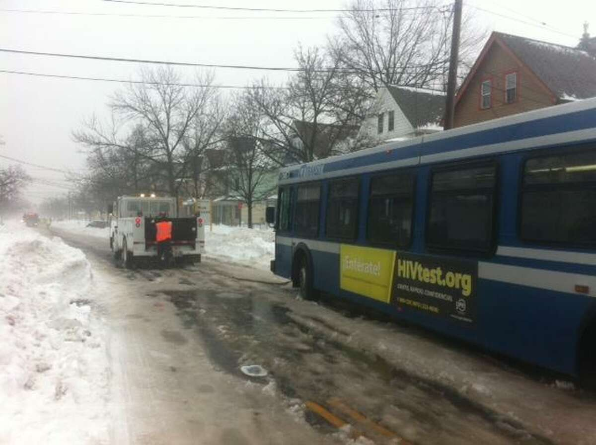 A tow truck attempts to help move a CT Transit bus that was stuck on an icy patch of road on Dixwell Avenue Monday afternoon. Photo by Rich Scinto