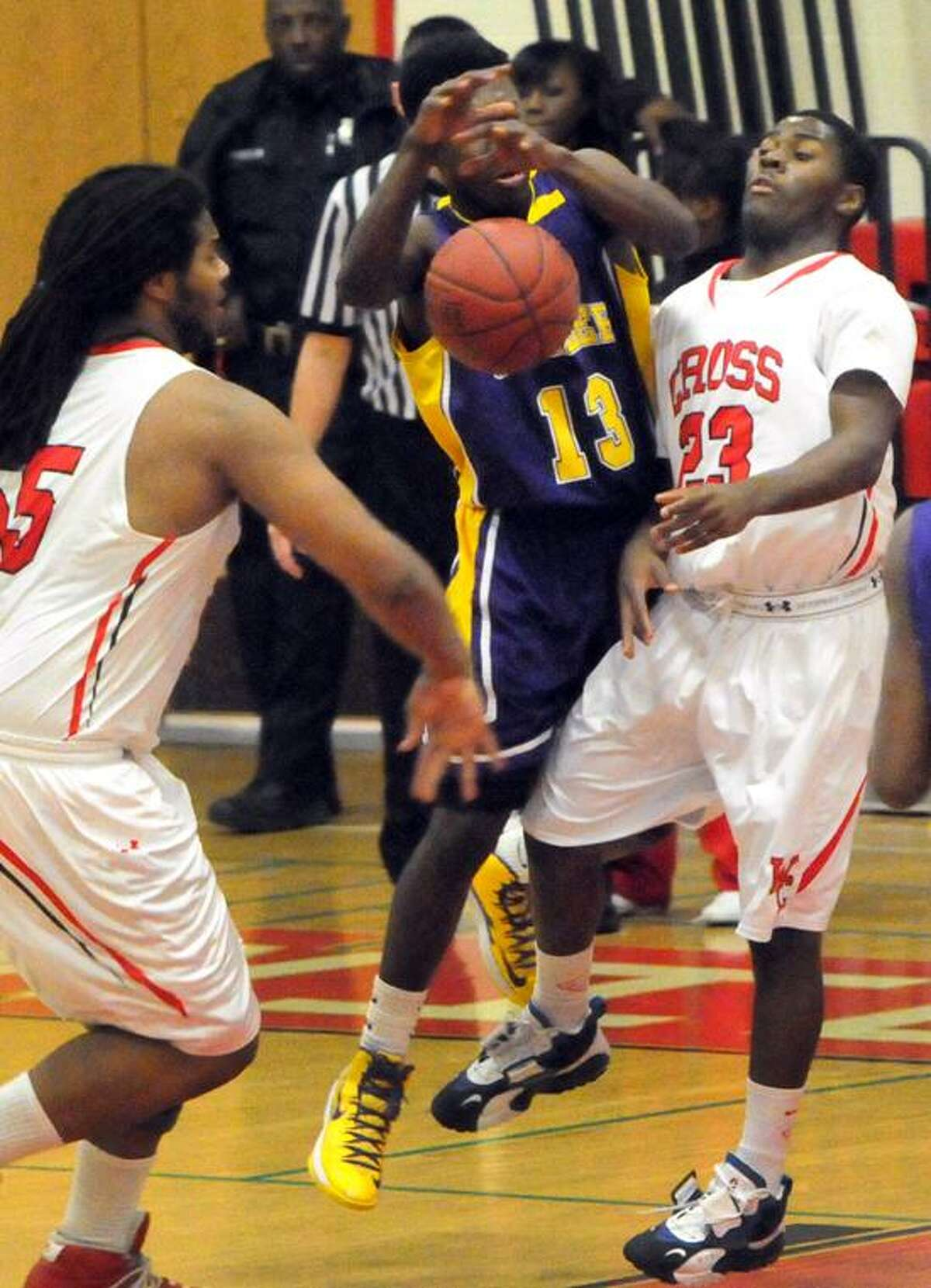 Jaelin Robinson, left, and teammate Jaylin Fuller, right, play tough defense against Amos Ford of Career Thursday evening. Cross remained No. 8 in the latest Register Top 10 poll. Photo by Peter Hvizdak / New Haven Register.