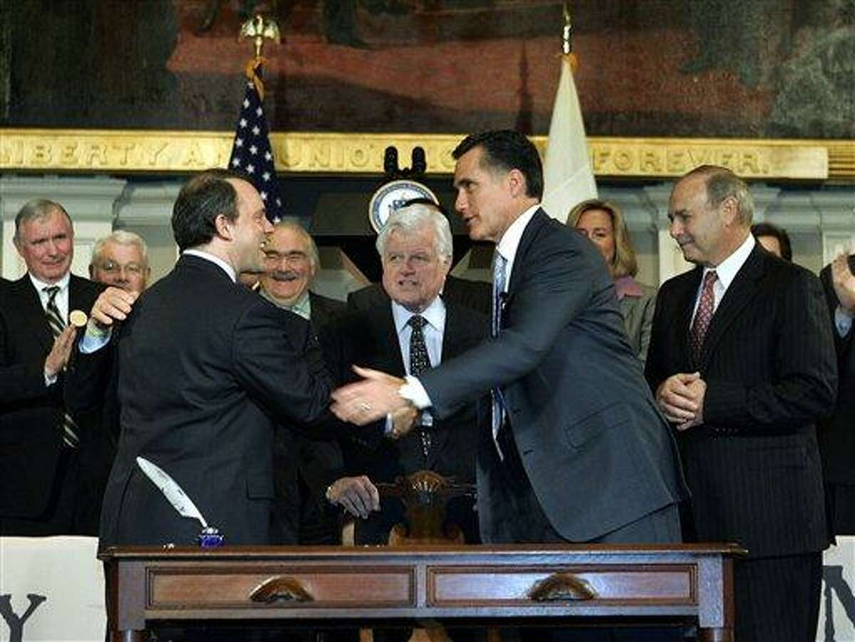 FILE - In this April 12, 2006 file photo, Massachusetts Gov. Mitt Romney, right, shakes hands with Massachusetts Health and Human Services Secretary Timothy Murphy after signing into law a landmark bill designed to guarantee that virtually all Massachusetts residents have health insurance at Faneuil Hall in Boston. Sen. Edward Kennedy, D-Mass., is center, and Massachusetts House Speaker Salvatore DiMasi, is at right. The Massachusetts law provides a model for the rest of the nation as states work to establish their own health exchanges in 2013. (AP Photo/Elise Amendola, File)