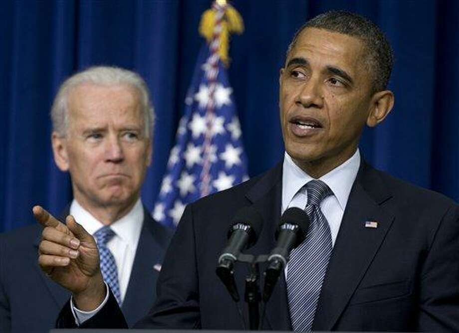 """FILE - In this Jan. 16, 2013 file photo, President Barack Obama, accompanied by Vice President Joe Biden, talks about proposals to reduce gun violence, in the South Court Auditorium at the White House in Washington. This is what """"Forward"""" looks like. Fast forward, even. President Barack Obama's campaign slogan is springing to life in a surge of executive directives and agency rulemaking touching many of the affairs of government. They are shaping the cost and quality of health plans, the contents of the school cafeteria, the front lines of future combat, the price of coal. They are the leading edge of Obama's ambition to take on climate change in ways that may be unachievable in legislation.  (AP Photo/Carolyn Kaster, File) Photo: AP / AP"""
