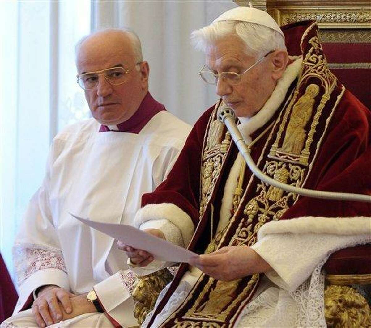 In this photo provided by the Vatican newspaper L'Osservatore Romano, Mons. Franco Comaldo, left, a pope aide, looks at Pope Benedict XVI as he reads a document in Latin where he announces his resignation, during a meeting of Vatican cardinals, at the Vatican, Monday, Feb. 11, 2013. Benedict XVI announced Monday that he would resign Feb. 28 - the first pontiff to do so in nearly 600 years. The decision sets the stage for a conclave to elect a new pope before the end of March. (AP Photo/L'Osservatore Romano, ho)