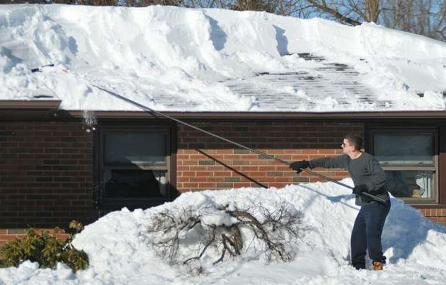 Catherine Avalone/The Middletown PressMiddletown resident Scott Sypek clears snow from the blizzard Nemo off the roof of his grandparents home Sunday afternoon. / TheMiddletownPress