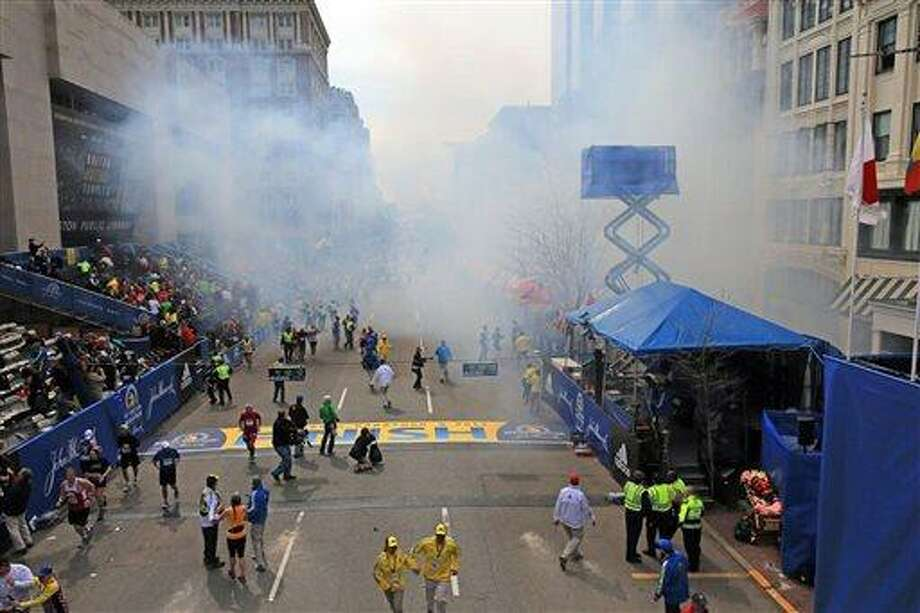 Medical workers aid injured people at the 2013 Boston Marathon following an explosion in Boston, Monday, April 15, 2013. Two explosions shattered the euphoria of the Boston Marathon finish line on Monday, sending authorities out on the course to carry off the injured while the stragglers were rerouted away from the smoking site of the blasts. (AP Photo/The Boston Globe, David L Ryan) Photo: AP / The Boston Globe