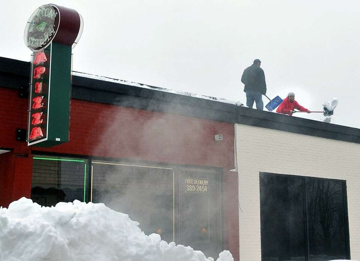 New Haven--Workers shovel off the roof of Dayton Street Pizza along Whalley Avenue, as heavy rains saturated the snow causing a dangerous condition for businesses and homes with flat roofs. Photo-Peter Casolino 2/11/13