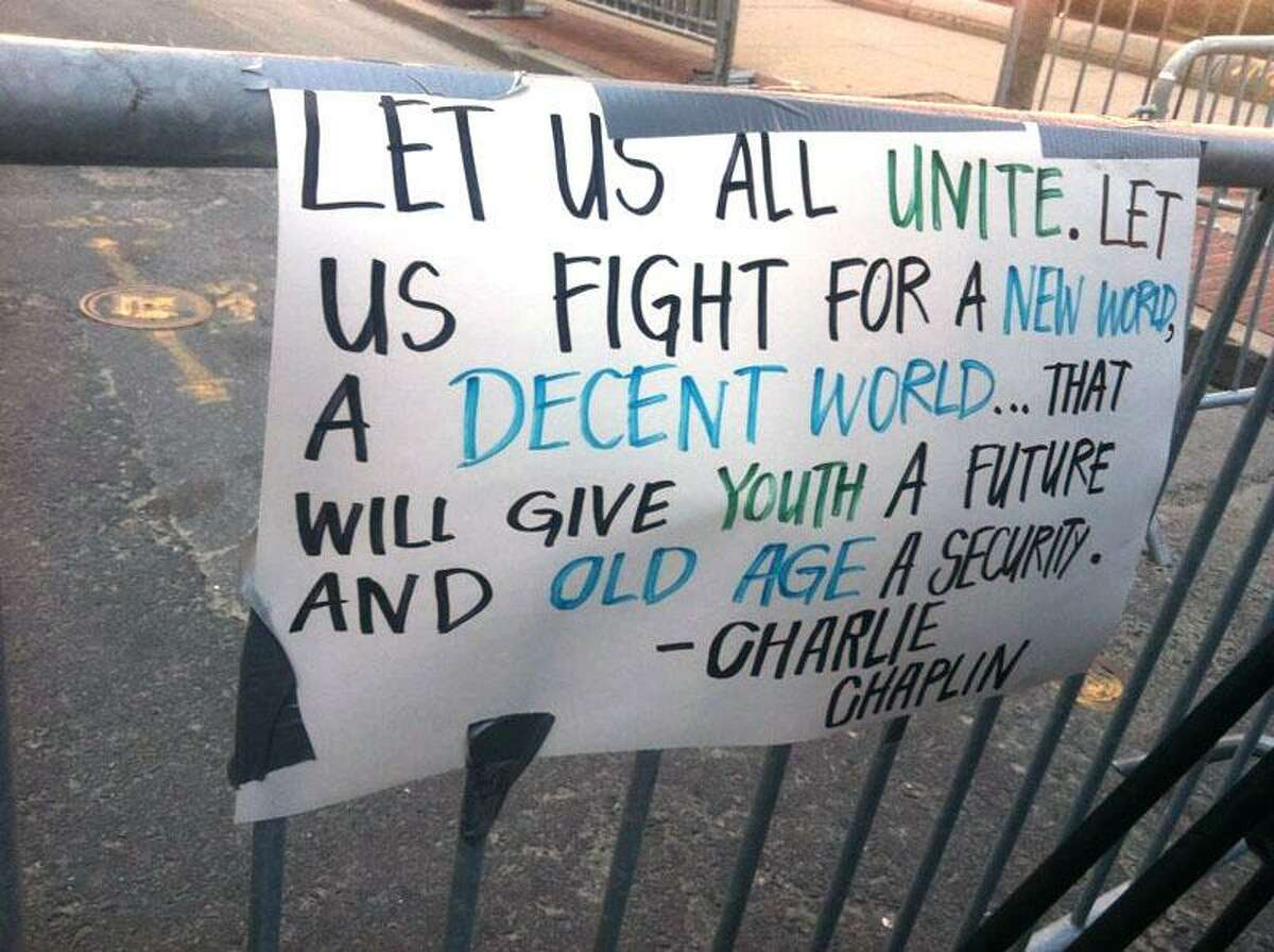 """Signs are taped to the barriers where hazmat teams investigate Wednesday in Boston. """"Let us all unite. Let us fight for a new world, a decent world ... that will give youth a future and old age a security."""" -- Charlie Chaplin"""