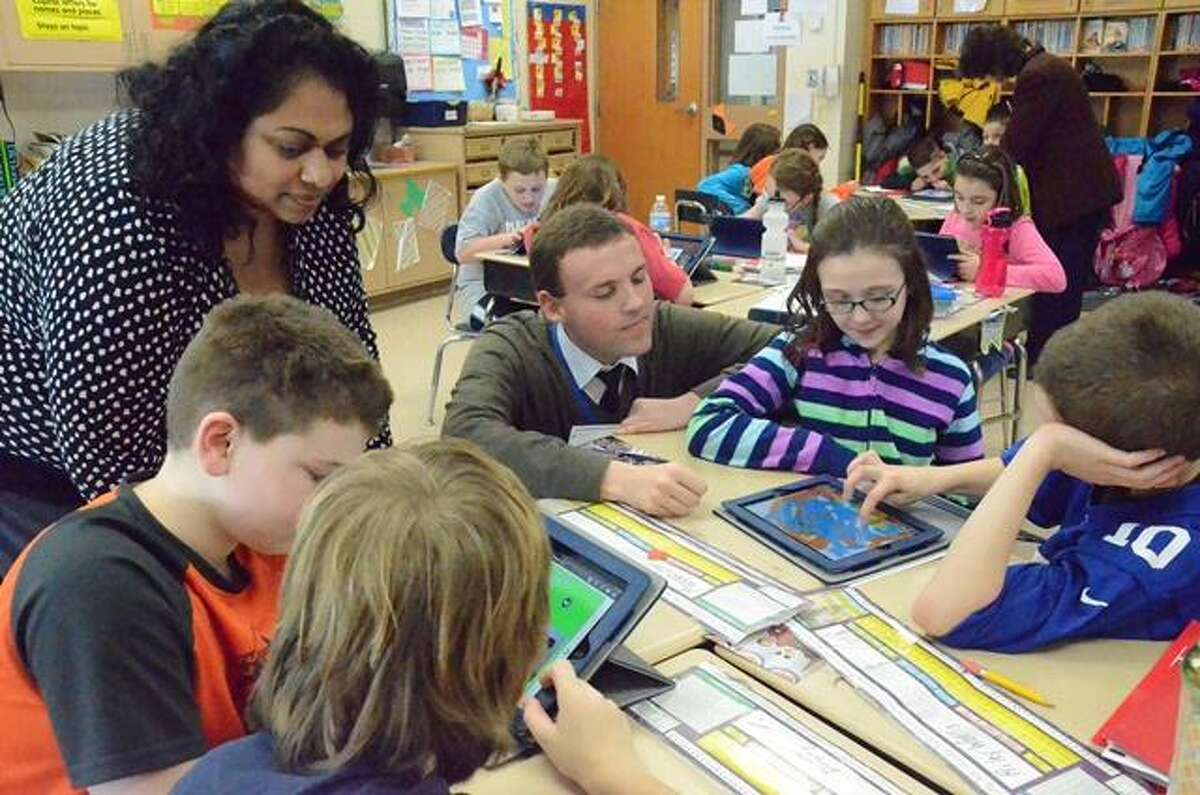 NICK WILL @DispatchNick // Oneida Dispatch Mr. Arthur and Kalpana Lennox instructing Seneca Street fourth graders Spencer Leland, Riley Wallis, Mayson Earl and Madison Shlotzauer on iPad use.