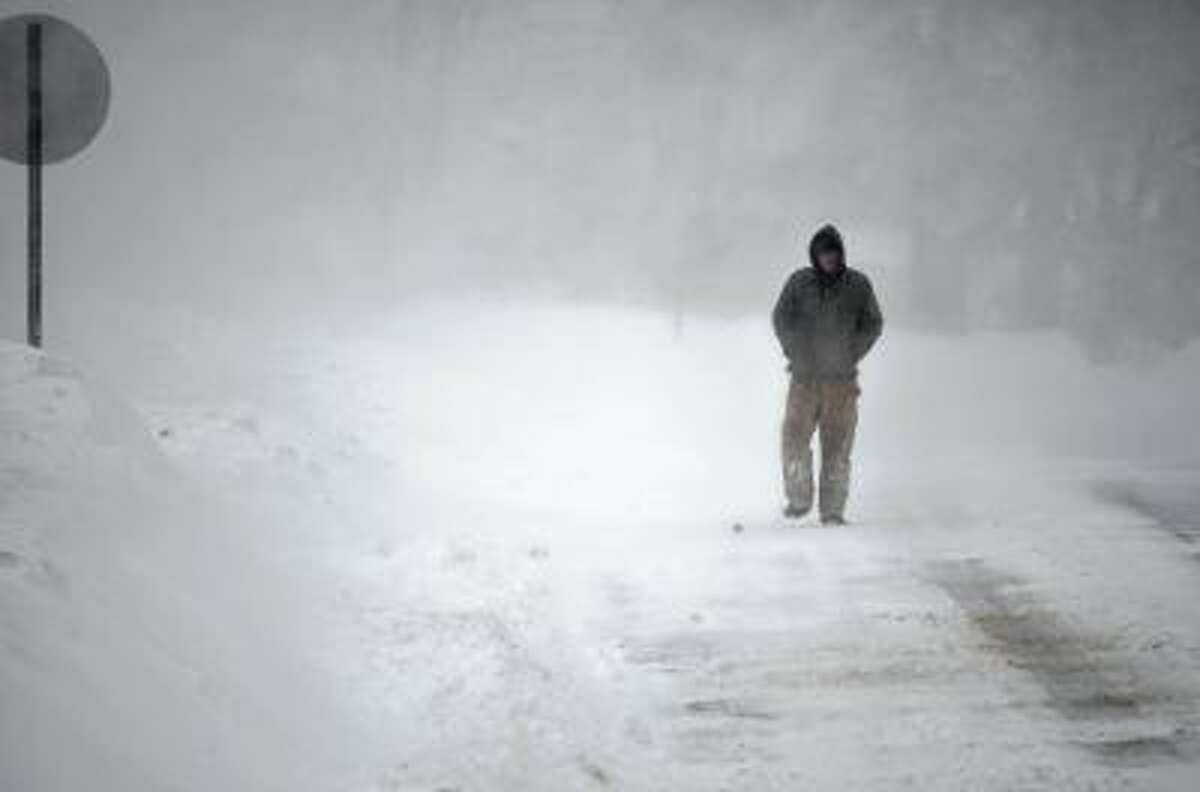 John Keenan of Terryville walks down Pearl St. in Torrington on Saturday morning. John Berry/Register Citizen