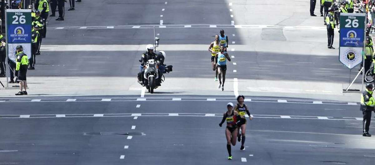 A motorcycle camera crew photographs the lead men's finishers as they pass the 26th mile marker, which was dedicated to the victims of the Sandy Hook Elementary School shooting in Newtown, Conn., during the 2013 running of the Boston Marathon in Boston, Monday, April 15, 2013. (AP Photo/Charles Krupa)
