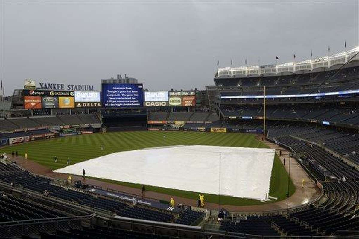 The infield a Yankee Stadium is covered by a tarp as tonights game between the New York Yankees and the Los Angeles Dodgers has been rescheduled due to inclement weather Tuesday, June 18, 2013, in New York. Tonight's game has been rescheduled for 1:05pm Wednesday, June 19, 2013. (AP Photo/Frank Franklin II)