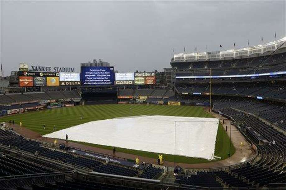 The infield a Yankee Stadium is covered by a tarp as tonights game between the New York Yankees and the Los Angeles Dodgers has been rescheduled due to inclement weather Tuesday, June 18, 2013, in New York. Tonight's game has been rescheduled for 1:05pm Wednesday, June 19, 2013. (AP Photo/Frank Franklin II) Photo: AP / AP