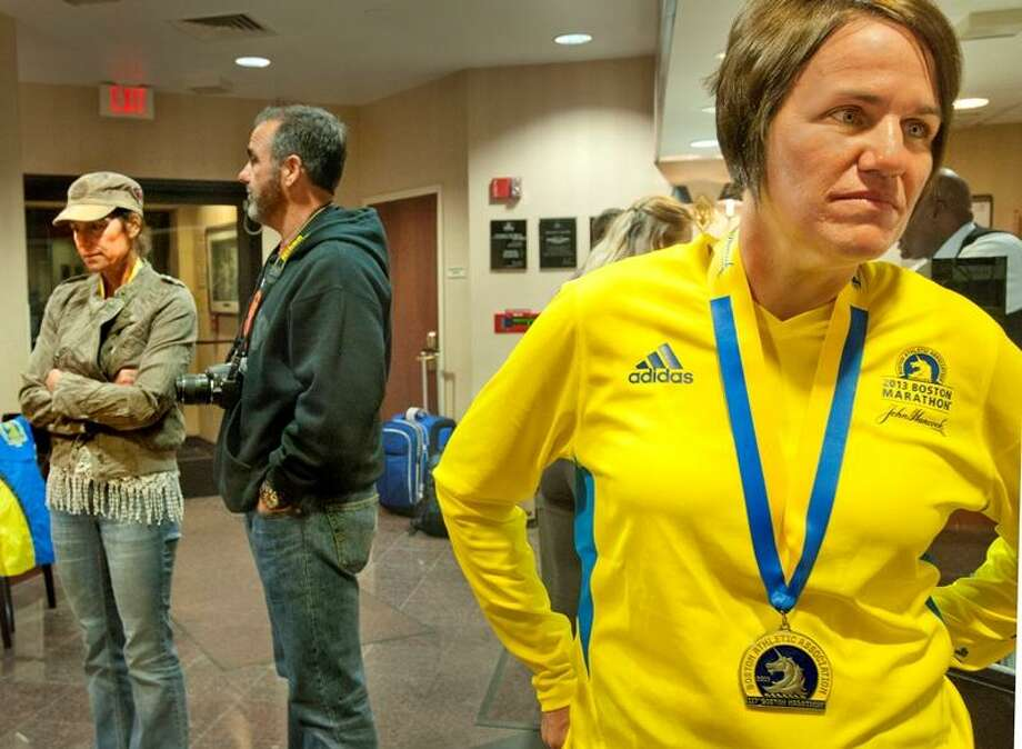 Boston -- Tracy Finn, right, finished the Boston Marathon 6 minutes before the explosion, as did her friend Lori Cundari,left. Dave Cundari, center, waited for his wife at a predetermined meeting place. He said a prayer while waiting. Finn is from Alron, Ohio. The Cundarises are from Lockeford, Calif. Melanie Stengel/Register