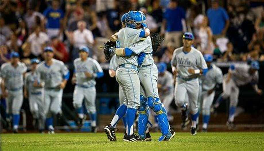 UCLA closing pitcher David Berg (26), left, hugs catcher Shane Zeile (14) following the Bruins' 2-1 victory over North Carolina State in game 8 of the College World Series at TD Ameritrade Park in Omaha, Neb., on Tuesday, June 18, 2013.  (AP Photo/The Omaha World-Herald/Ryan Soderlin) Photo: AP / OMAHA WORLD-HERALD