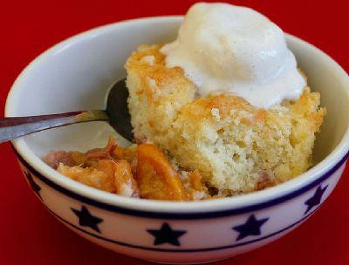 Peach cobbler with vanilla ice cream. A cobbler is a dessert consisting of sugared fruit topped with a sweetened biscuit topping. Illustrates HOWTO-COBBLER (category d), by L.V. Anderson (c) 2013, Slate. Moved Monday, June 17, 2013. (MUST CREDIT: Slate photo by Ellie Skrzat.)