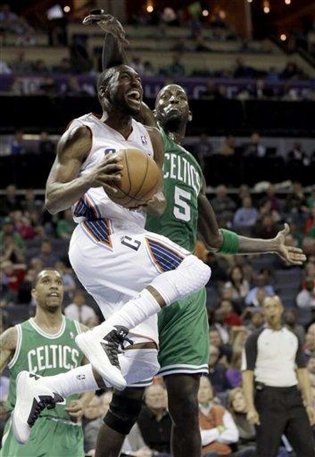 Charlotte Bobcats' Kemba Walker, front, drives past Boston Celtics' Kevin Garnett, rear, during the first half of an NBA basketball game in Charlotte, N.C., Monday, Feb. 11, 2013. (AP Photo/Chuck Burton) Photo: ASSOCIATED PRESS / AP2013