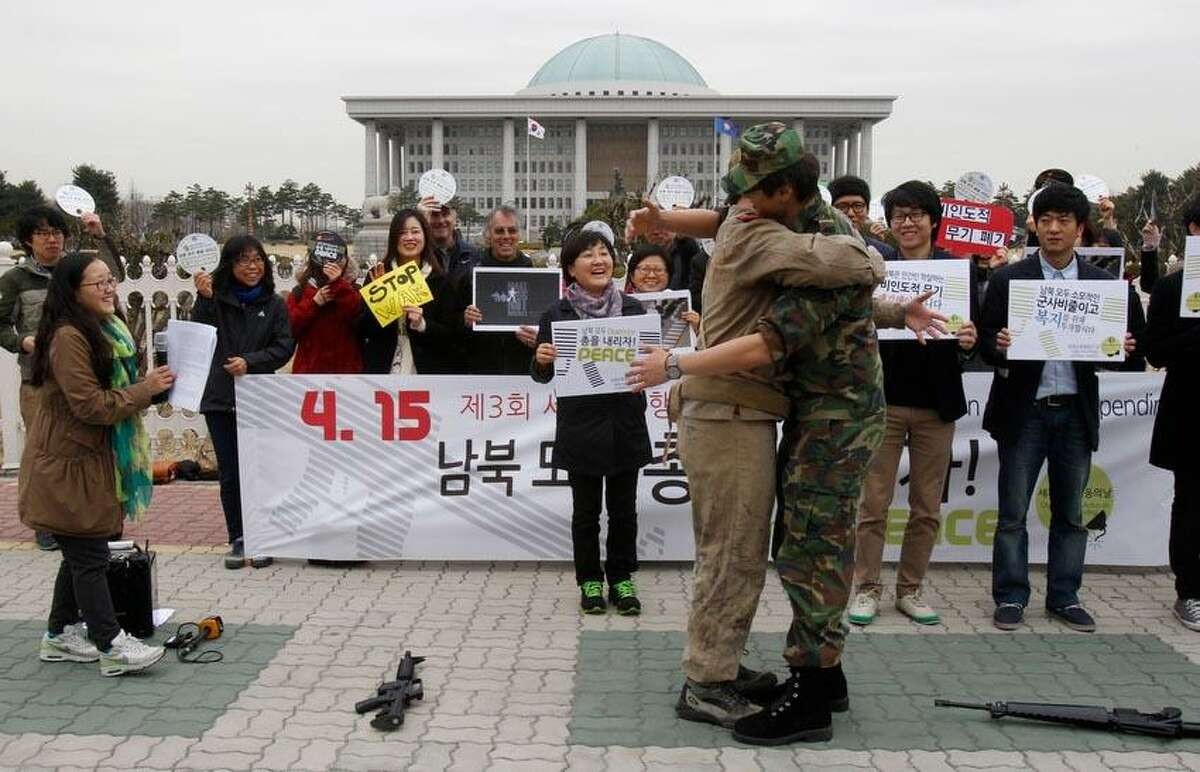 Anti-war activists wearing military clothes of a North, left, and South Korea hug each other during a rally to mark Global Day of Action on Military Spending in front of the National Assembly in Seoul, South Korea, Monday, April 15, 2013. They demanded peaceful unification of the Korean peninsula. Elsewhere in the region, however, the focus remained on the threat of a missile launch by the North as U.S. Secretary of State John Kerry wrapped up a tour to coordinate Washington's response with Beijing, North Korea's most important ally, as well as Seoul and Tokyo. (AP Photo/Ahn Young-joon)