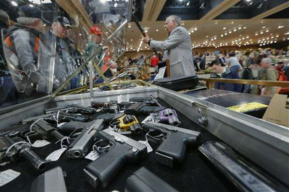 Handguns appear on display Jan. 26 at the table of David Petronis of Mechanicville, N.Y., standing with rifle, who owns a gun store, during the heavily attended annual New York State Arms Collectors Association Albany Gun Show at the Empire State Plaza Convention Center, in Albany, N.Y. Key measures of New York's tough new gun law are set to kick in, with owners of guns now reclassified as assault weapons required to register the firearms and new limits on the number of bullets allowed in magazines. As the new provision takes effect April 15, New York's affiliate of the National Rifle Association said it plans to head to court to seek an immediate halt to the magazine limit. Associated Press file photo Photo: AP / FR170784 AP